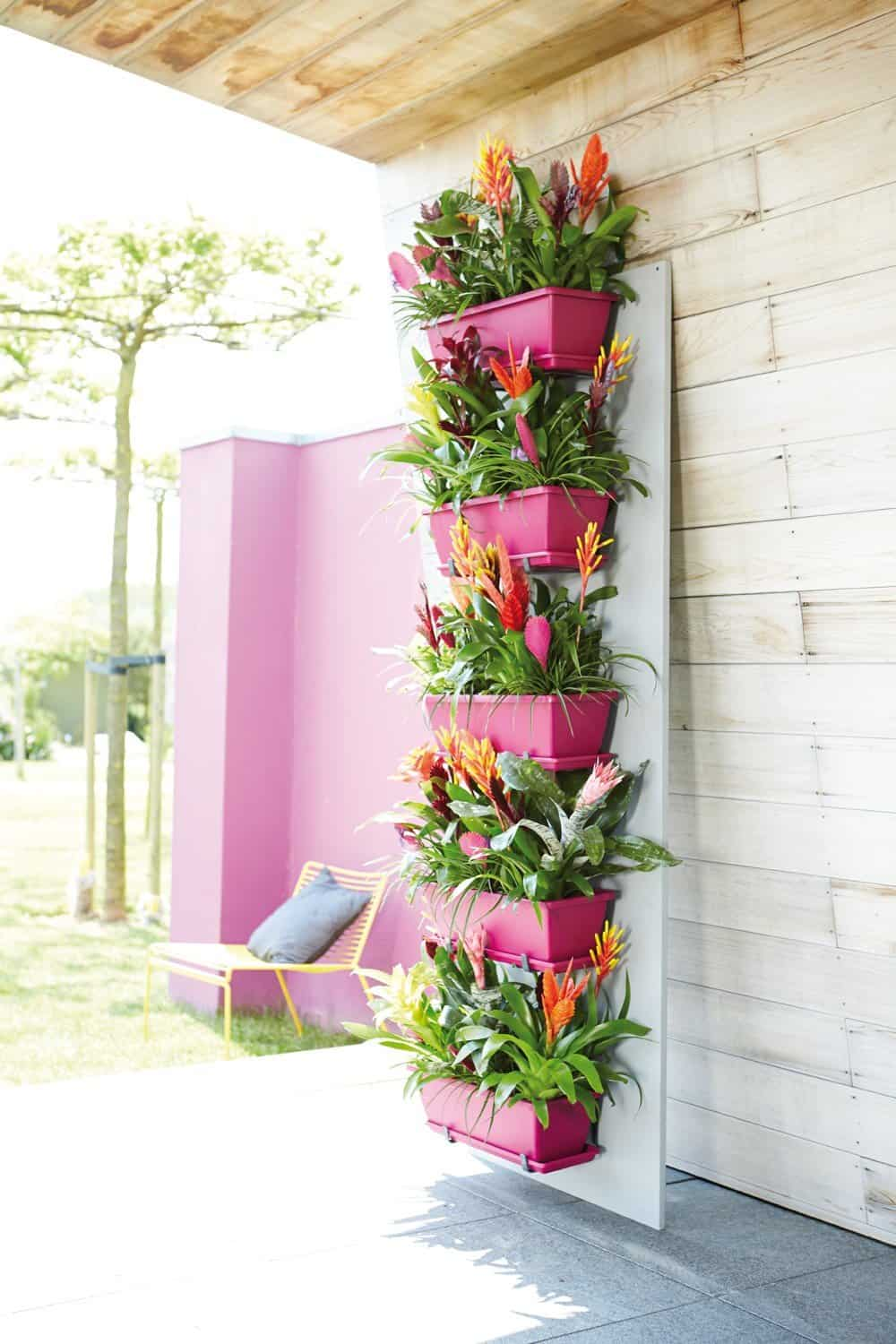03-bright-pink-adds-a-pop-of-color-and-accents-vibrant-bromeliads-vertical-garden
