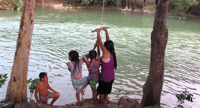 Kids playing with Rope swing at lake