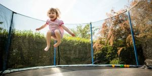 child enjoys jumping at a trampoline