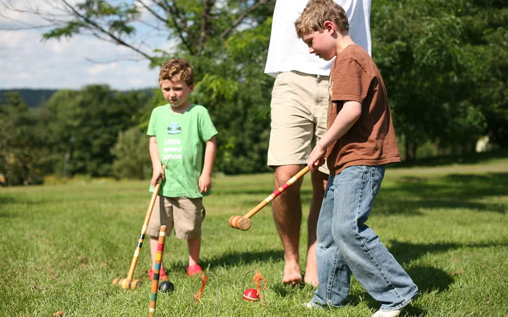 children playing croquet in the backyard