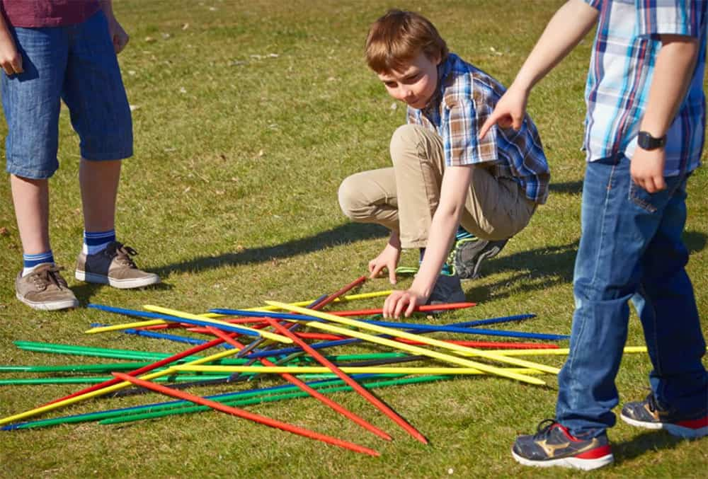 children playing giant pickup sticks in the backyard