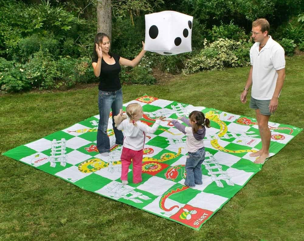 family playing giant snakes and ladders