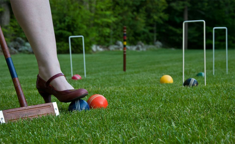 woman stepping on a croquet ball