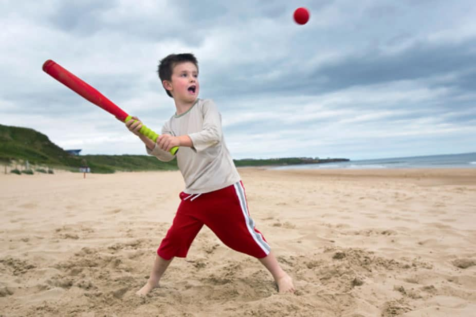 boy playing rounders on the sand