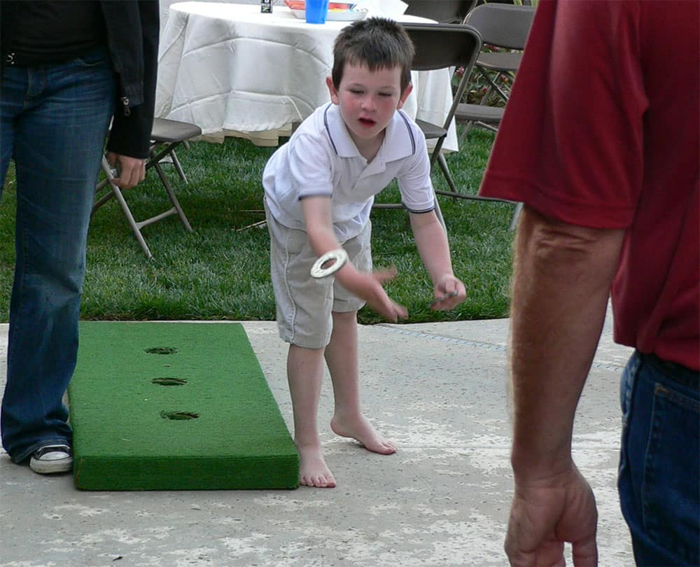 kid playing washer toss game