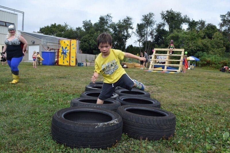 kid running on a tire obstacle course