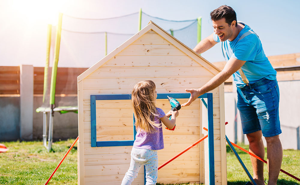 father and daughter assembling a wooden playhouse