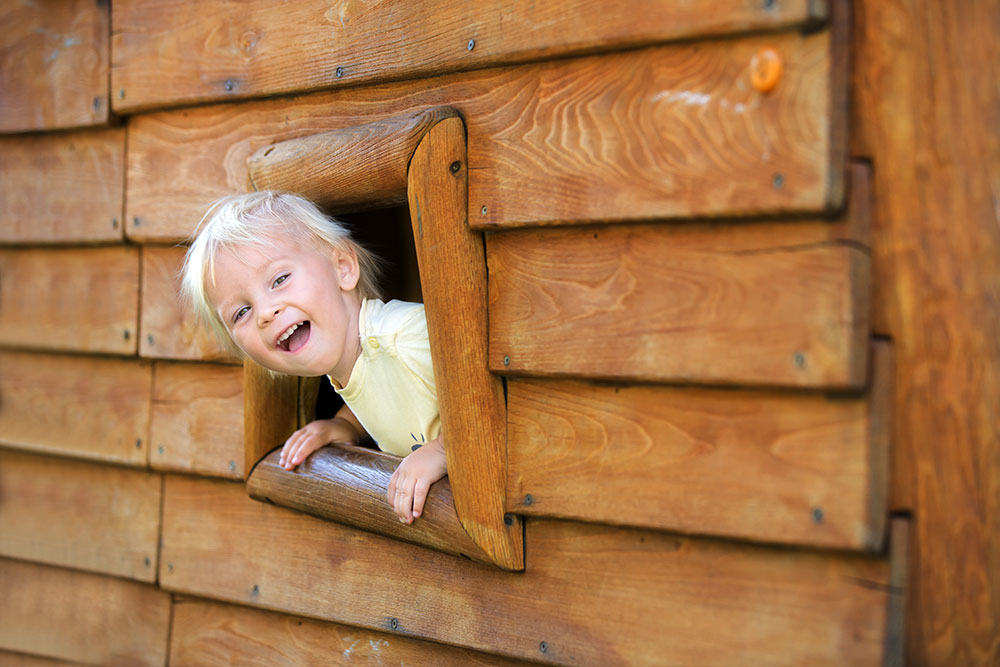 happy kid inside wooden playhouse