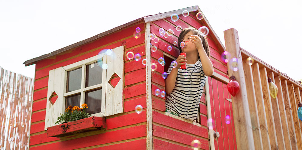 young boy blowing bubbles in a wooden playhouse